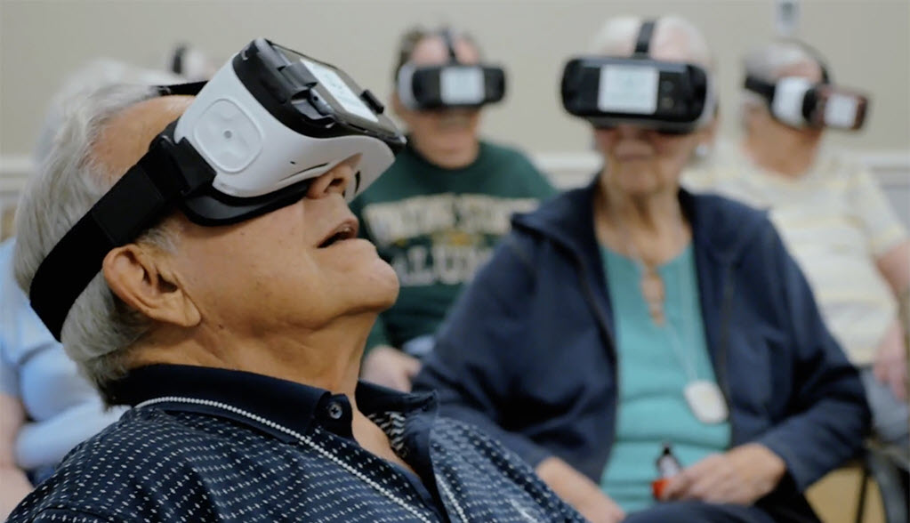 older people in virtual reality headset with a man in foreground